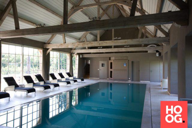 Rechthoekig binnen zwembad met loungestoelen en houten