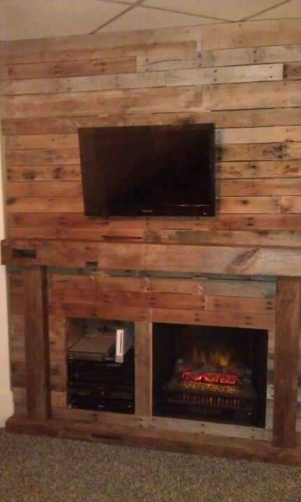 with real beam mantel on an all pallet wood wall