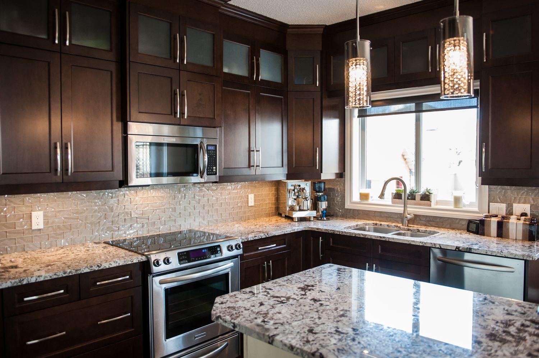Dark espresso kitchen quartz counter tops pendant lights sink