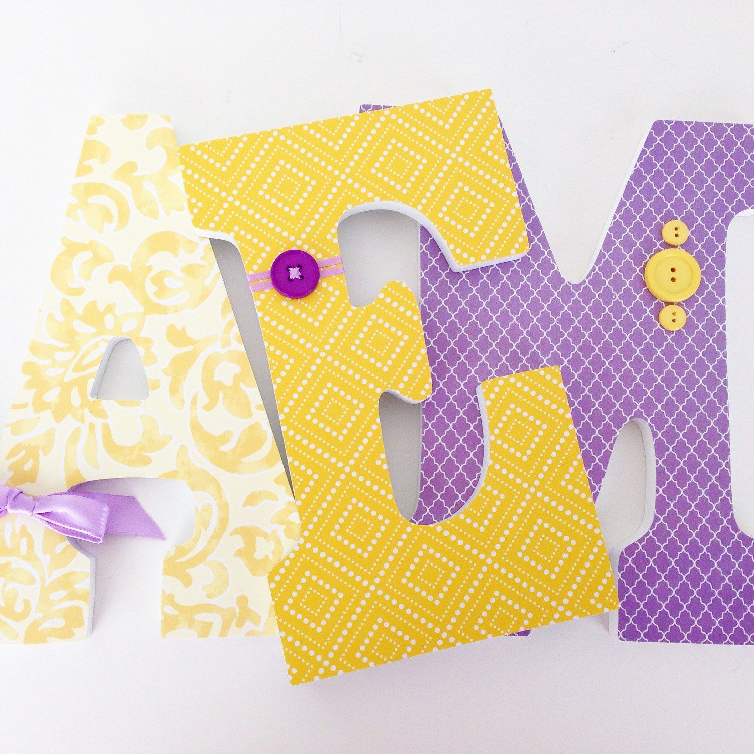 Yellow and lavender letters with button and bow embellishments ...