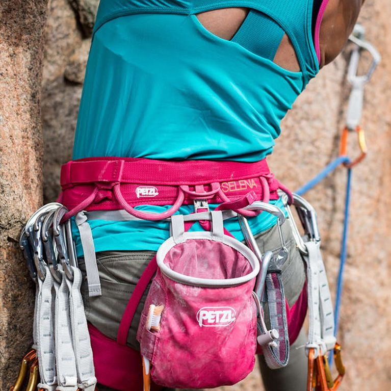 A woman lead climbs an outdoor route with a Raspberry Petzl Selena