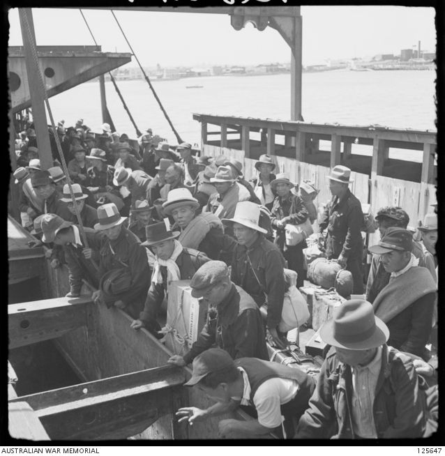 PORT MELBOURNE, VIC. 1946-02-21. A GROUP OF JAPANESE MALE INTERNEES WAITING TO GO BELOW DECK OF THE KOEI (KOEYI) MARU. THE SHIP, A FORMER JAPANESE MINELAYER STILL CREWED BY NAVAL PERSONNEL, ARRIVED ...