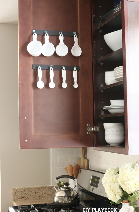 Organize your kitchen with this easy DIY project. All you need are free paint stirrers, velcro strips, and some hooks to organize your measuring cups and spoons!