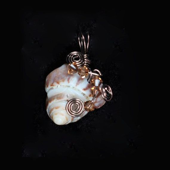This spiral sea shell is unique. It is wire-wrapped and has 5 amber colored Swarovski crystals. It is $22.00