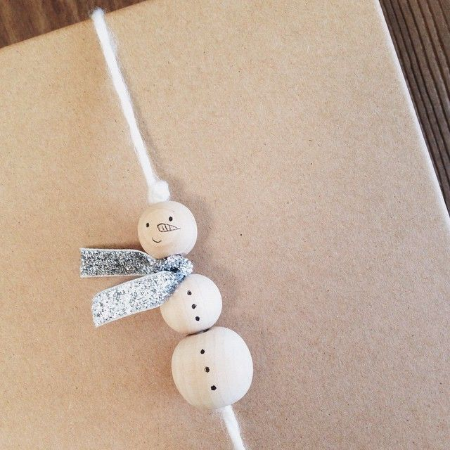 """Keep little hands busy with this simple DIY snowman gift topper (can also double as a tree ornament). Have your kiddos use a fine-tipped pen or marker to draw faces and """"buttons"""" onto three wooden beads. Thread beads onto a length of yard or ribbon, tie a thick knot at the top and bottom to hold in place, and then tie a snippet of ribbon around your snowman's neck to finish. Attach to a gift or hang on the tree! The more homemade your snowmen look...the more charming they will be!"""