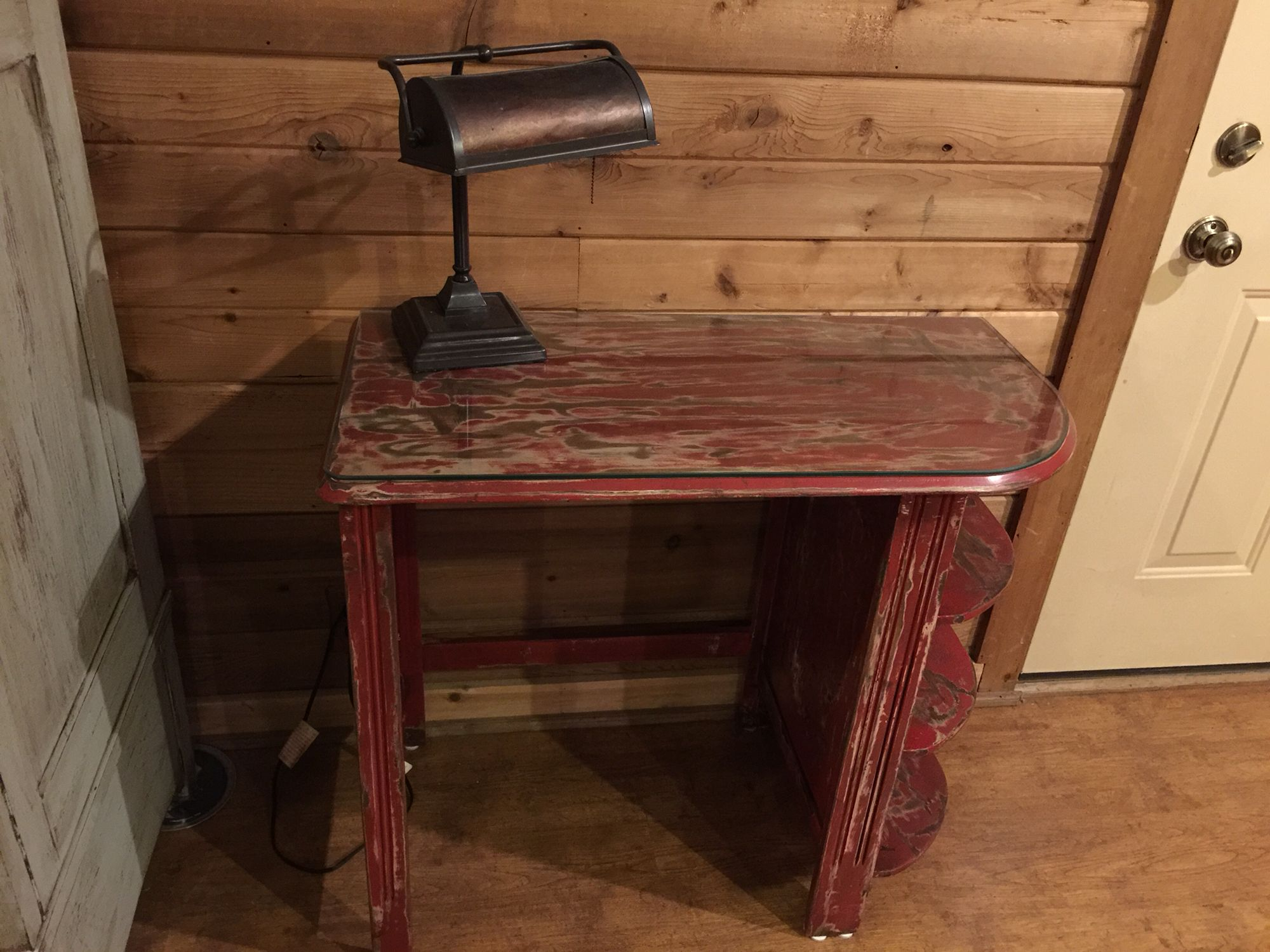 """Cute open sided red desk heavily distressed and sealed with polyurethane with a custom glass top. Desk:17.5"""" deep X 35"""" wide X 31"""" tall"""