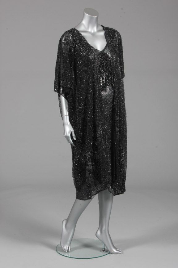 A black beaded dress and evening coat, late 1920s, the dress with irridiscent black beads overall with asymmetric hem, large 19th century jet beaded medallion to the chest, bust approx 86cm, 34in; the tulle evening coat covered in black and silvery seed beads, with draped batwing sleeves and foliate designs to the shoulders and hem | Kerry Taylor Auctions