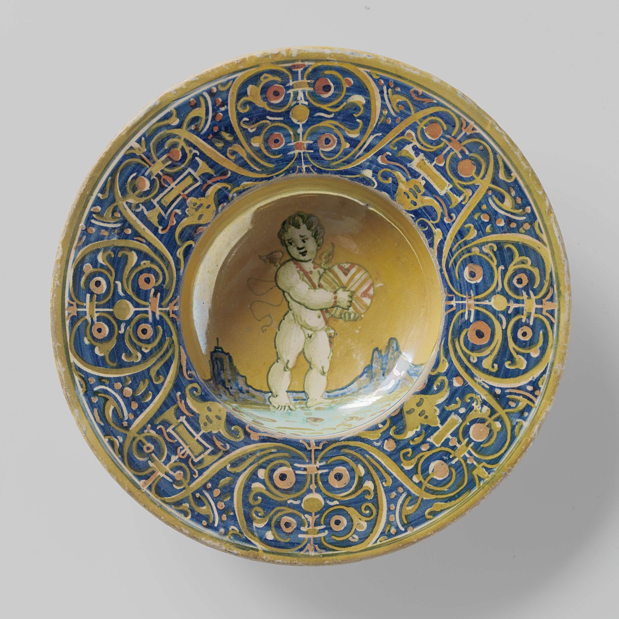 Anonymous | Bord met verdiept plat met veelkleurig beschilderde  putto met bol in beide handen. Op de rand een arabeskenachtig rankenpatroon., Anonymous, c. 1530 | Rond bord van veelkleurig beschilderde majolica, met een verdiept plat. Op het plat is een putto met een bol in beide handen geschilderd op een grond van goudluster. Op de brede rand is een zich herhalend arabeskenachtig rankenpatroon geschilderd in rood en goudluster op een blauwe fond.