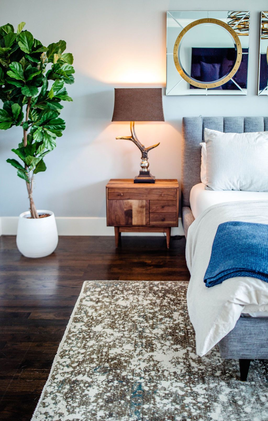 Master bedroom with wood floors, blue throw blanket and
