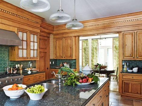 Honey colored pine cabinetry and dark green backsplashes for Traditional english kitchen design