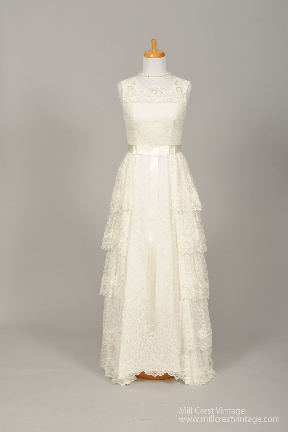 Designed in the 50's, this sweet vintage wedding gown is done in a floral lace over an acetate lining. The sleeveless bodice offers a scalloped scooped neckline and back. The long, asymmetrically cut