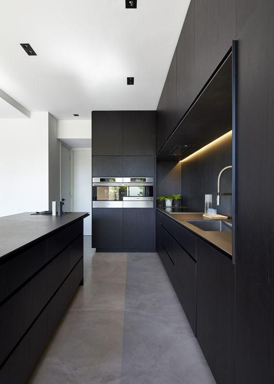 The Kitchen Space Features Blacked Out Custom Cabinetry With A Black Kitchen  Island That Allows For Seating And Serving.