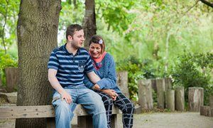 Bartek and Jessica, who are in a relationship, sitting on a bench under a tree