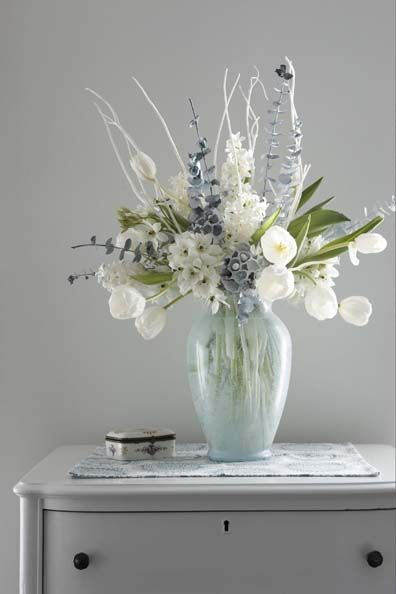 a pale winter floral arrangement is created with green eucalyptus