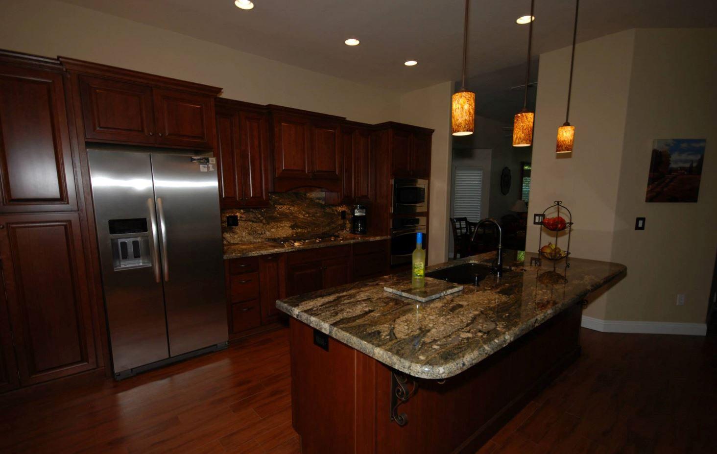 Cardell Cherry Cabinets With Nutmeg Stain And Tiramisu Granite With Waterfall Edge Granite Kitchen Cherry Cabinets Kitchen Cabinets In Bathroom