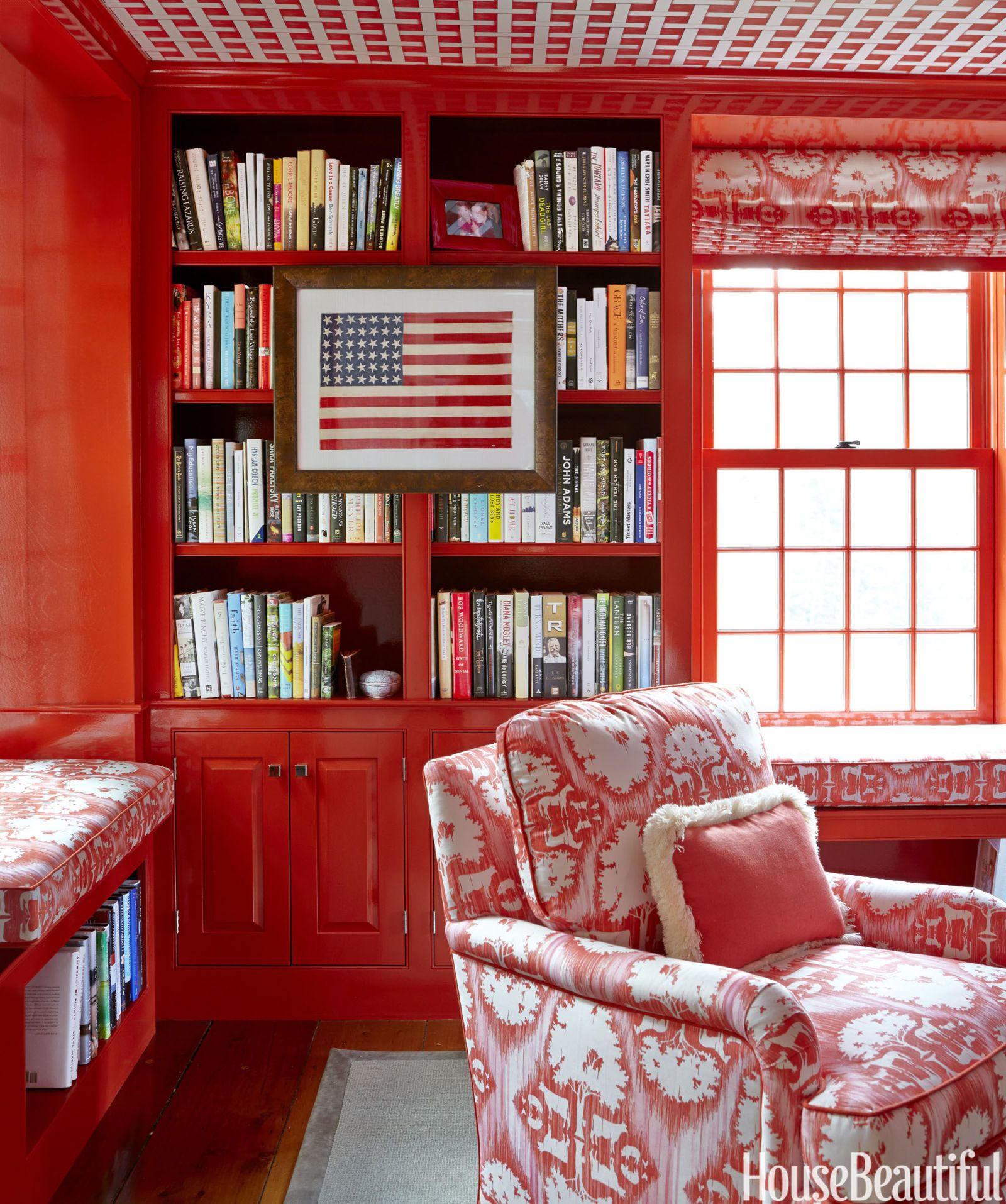 Using one fabric in the library — Farmyard Strie by Ramsay Gourd Home — on the chairs, sofa, window seats, and shades makes for a cozy, cohesive room. The cambridge chair, topped with a trimmed, red pillow, is by the Charles Stewart Company.    - HouseBeautiful.com