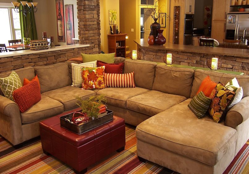 A warm living room featuring green and orange earth tones and rustic stone work by Lindsay Hoekstra West Michigan interior designer.