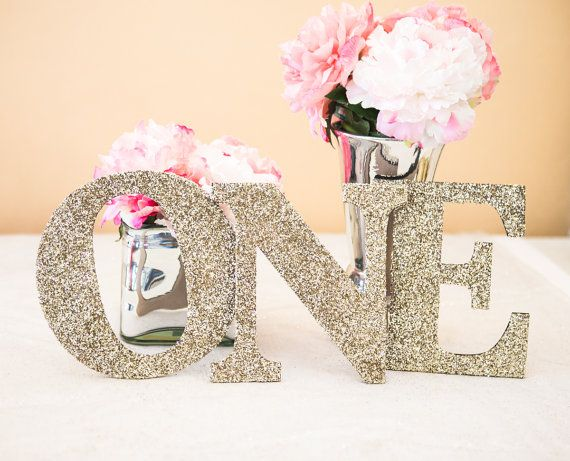 This one sign in glitter says ONE and is perfect for your little ones first birthday, whether on display at the party or used for a photo shoot! Cut in wood and glittered in your choice color, this wooden letters decoration is sure to bring smiles to everyones faces! SIZE: 8 tall and