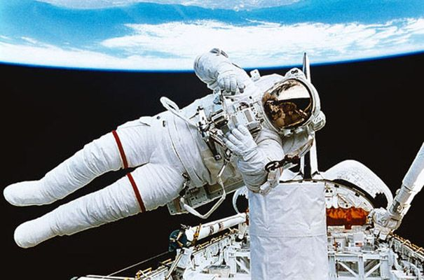 Elegant Astronaut Floating In Space Wall Mural. Earth In Background. Part 23