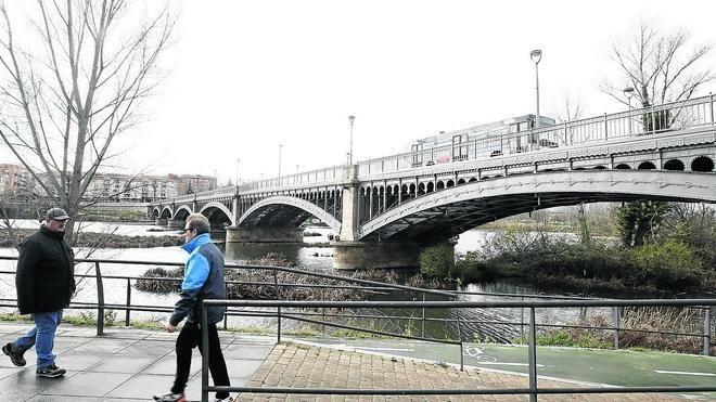 Dos personas pasean por el parque fluvial, junto al puente de Enrique Estevan.