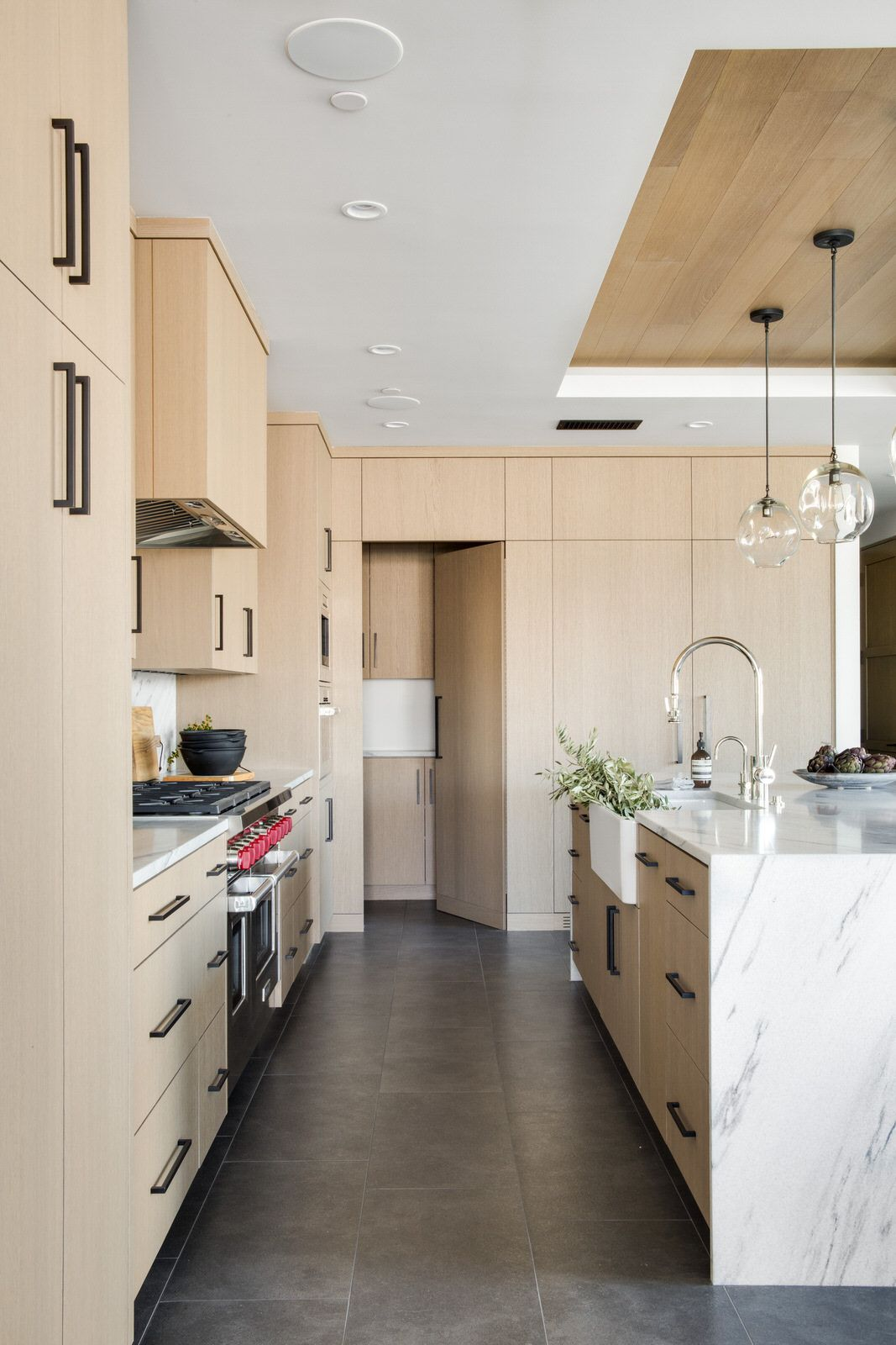 White Oak Kitchen Cabinets With Waterfall Marble Island Design By Chad Mellon White Oak Kitchen Oak Kitchen Cabinets Brown Kitchen Cabinets