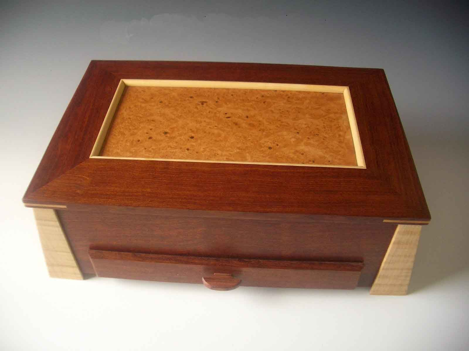 Boxshaped jewelry box with angled legs a lid that lifts up and a