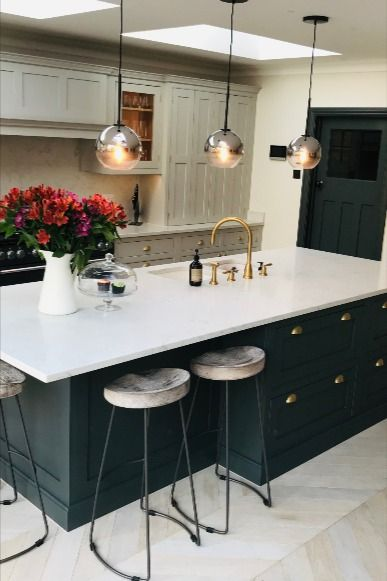 Dark green kitchen island with white worktops, built-in sink and gold fittings