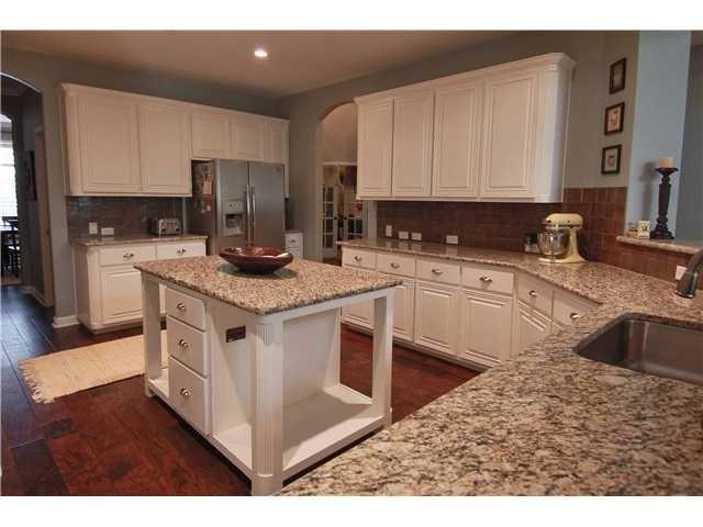 love white cabinets with dark floors and granite kitchen