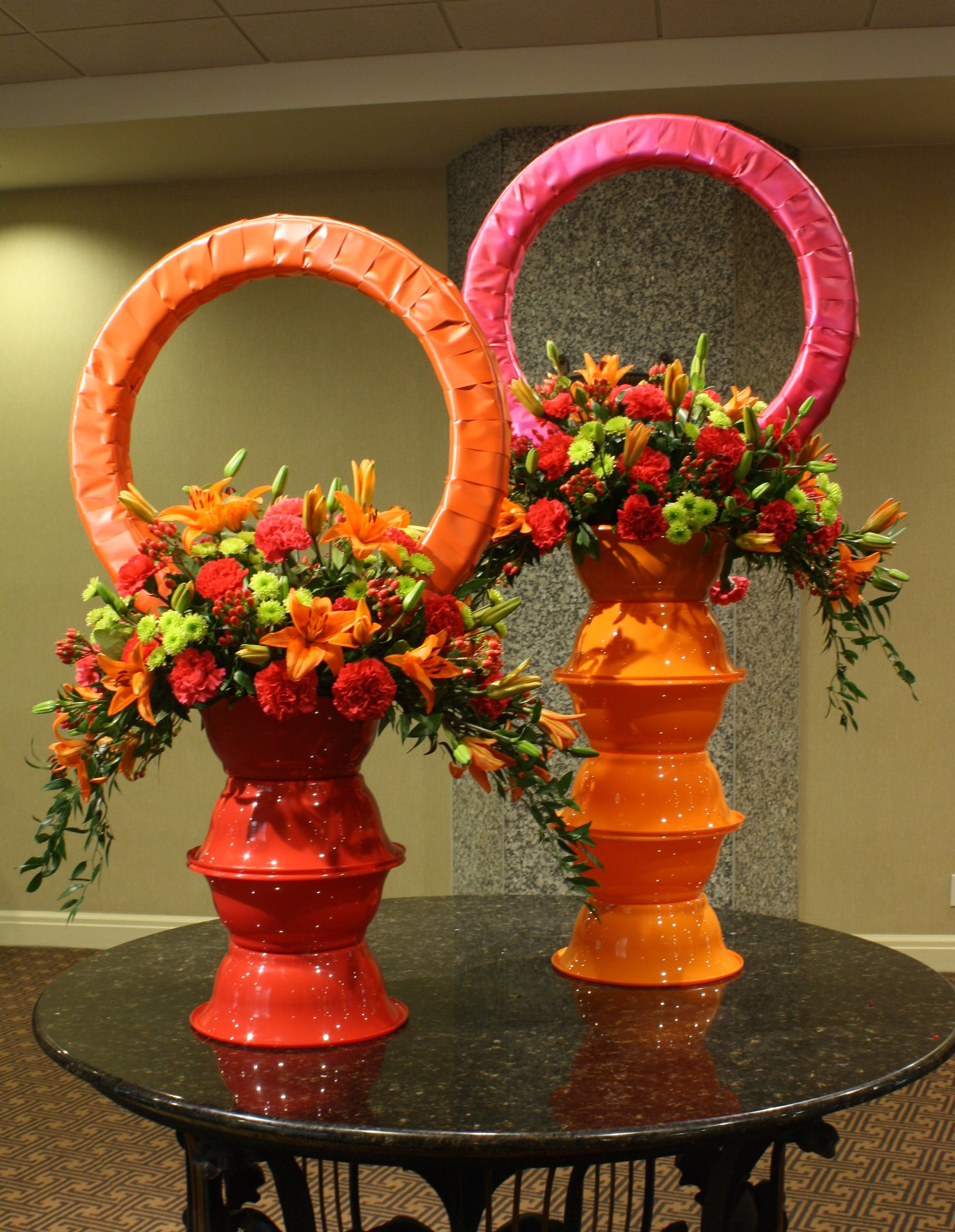 """""""VIVID PASSION""""  Tom Kenison AIFD  Colorful Plastic bowls from the dollar store are stacked upon each other to make the pedestals which support the vividly colored crescent shaped arrangements.  Ribbon wrapped wreaths add personality and completes the composition"""