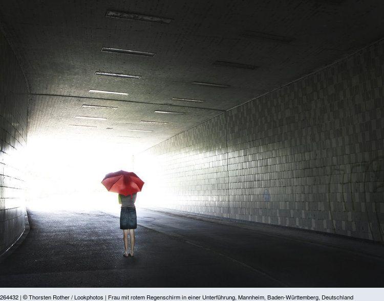 frau mit rotem regenschirm in einer unterführung mannheim