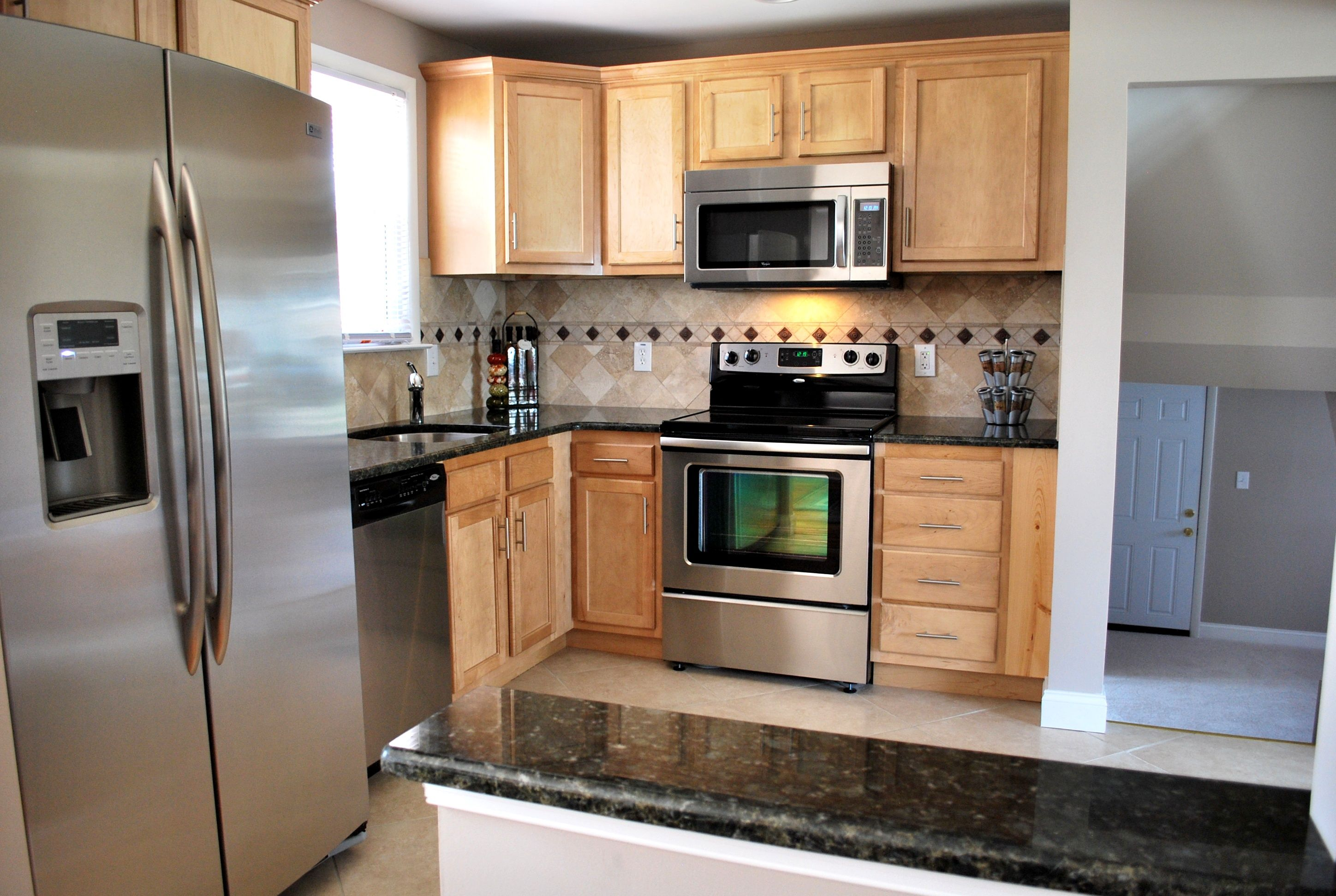 Light maple cabinets pair well with dark granite ... on Backsplash For Maple Cabinets And Black Granite  id=97889