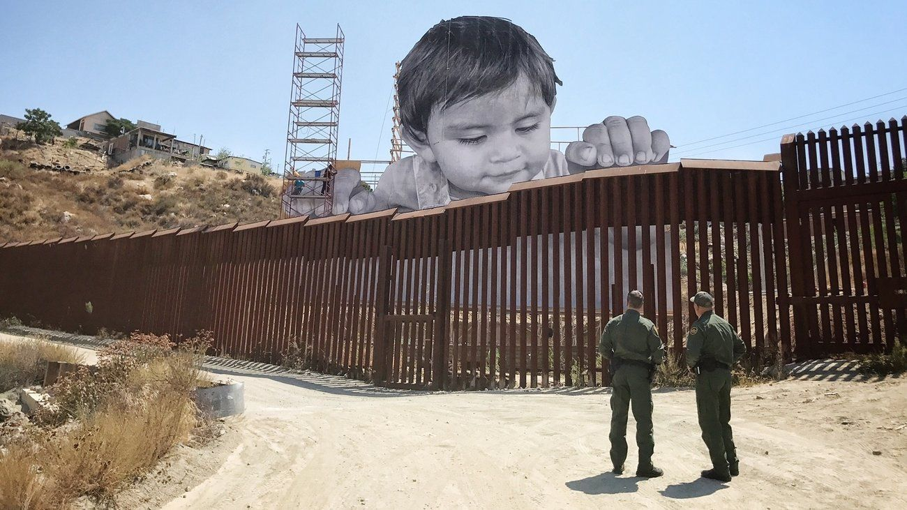 As Boy Peers Curiously Over Border Wall, His Artist Asks