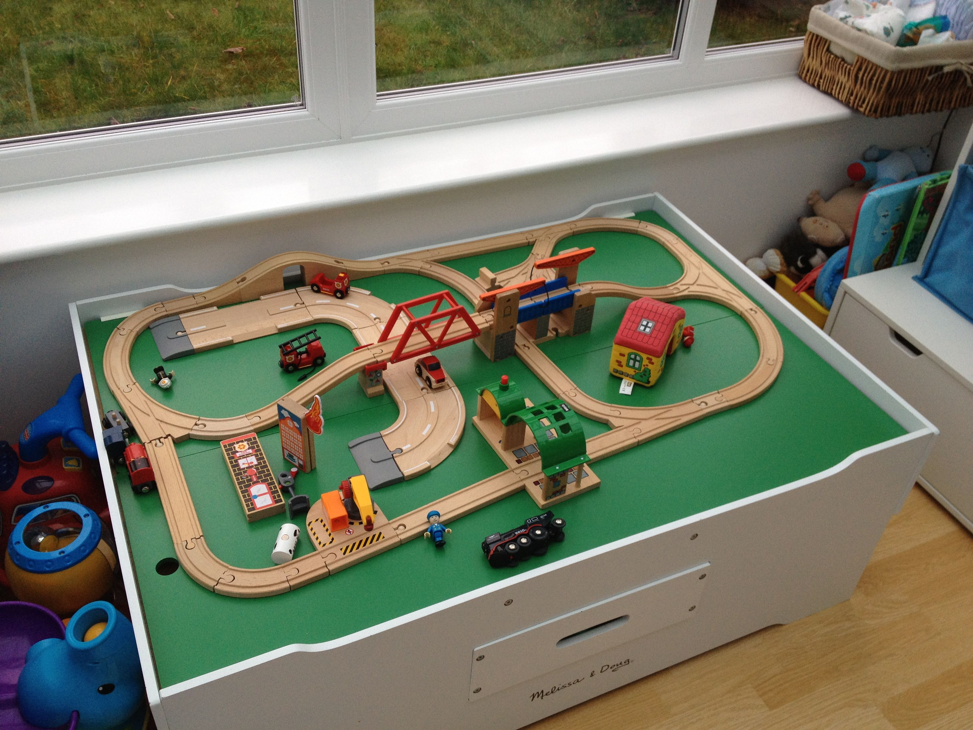Theres a fire in a building by the side of the wooden train set