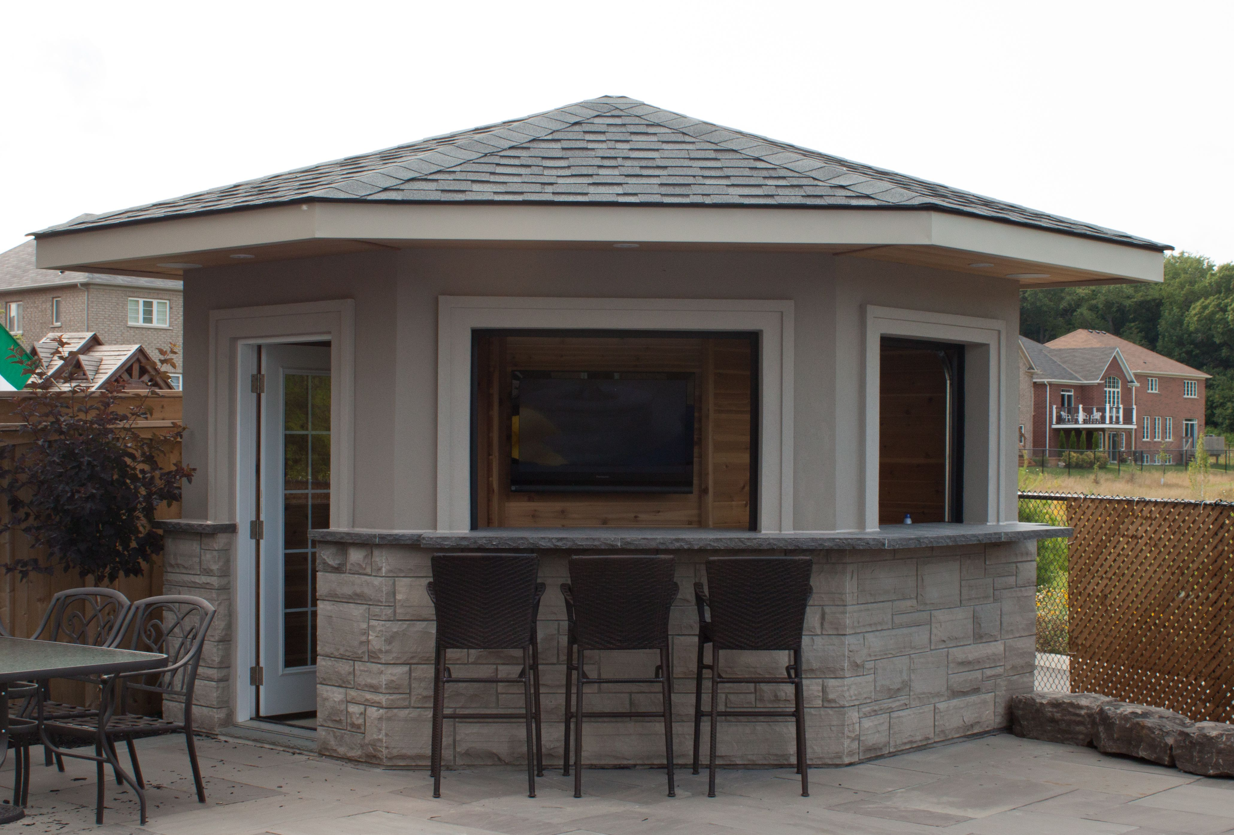 5 sided shed pool house cabana featuring stucco exterior and garage
