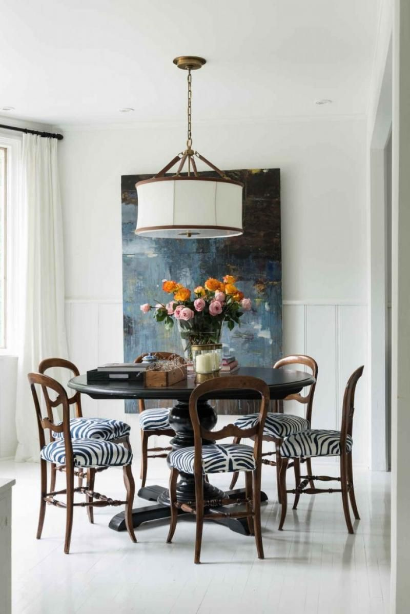 Warm dining room with wall art and zebra print padded chairs ...