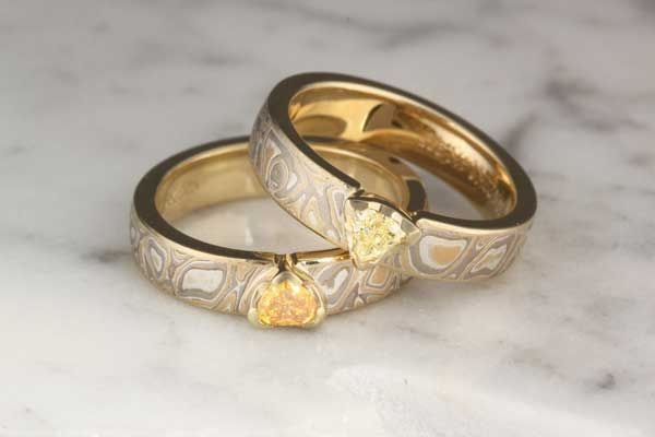 Hers & Hers Mokume Solitaire Straight Tapered Head Engagement Rings with trillion center stones