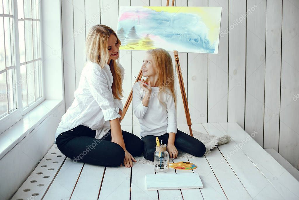 Beautiful mom and daughter are drawing stock photo