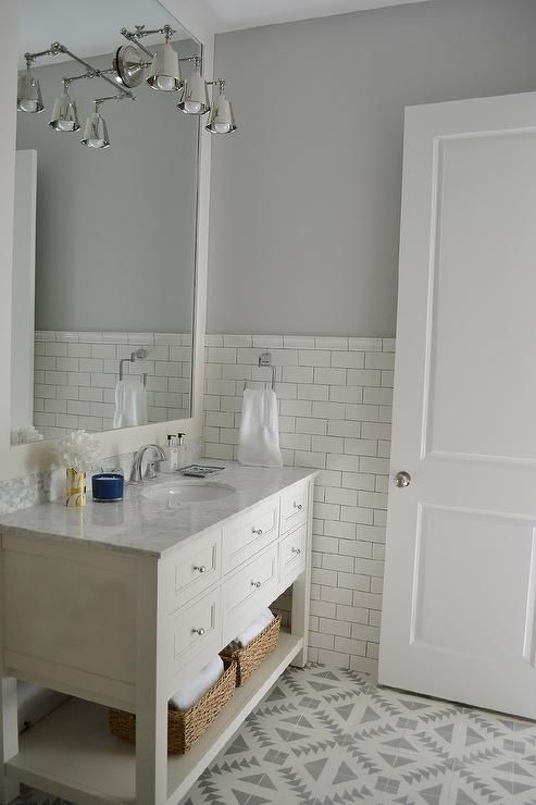 White and gray bathroom features top half of walls painted gray and bottom half of walls clad in white subway tiles lined with a white washstand fitted with a shelf topped with carrera marble under a full height framed mirror illuminated by a three light sconce alongside a Cement Tile Shop Tulum II Tile floor.
