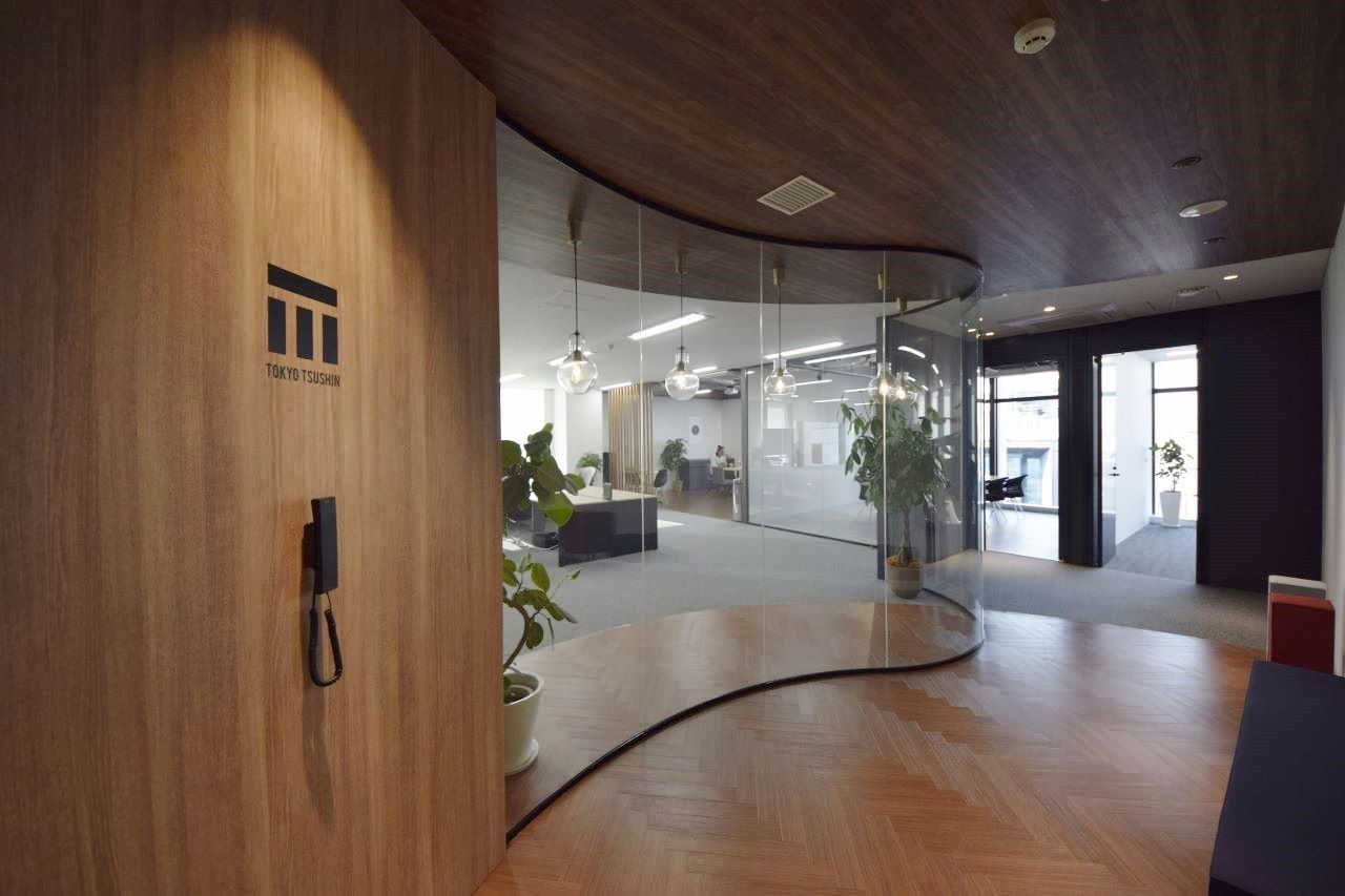 Rガラスの美しい曲線 木目とスケルトン天井の開放オフィス