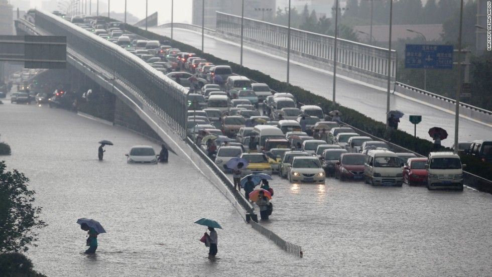 Heavy rains force people to walk across a flooded road and leave vehicles trapped on a viaduct in Wuhan, the capital of Hubei province in central China, on Sunday, July 7. CNN.com