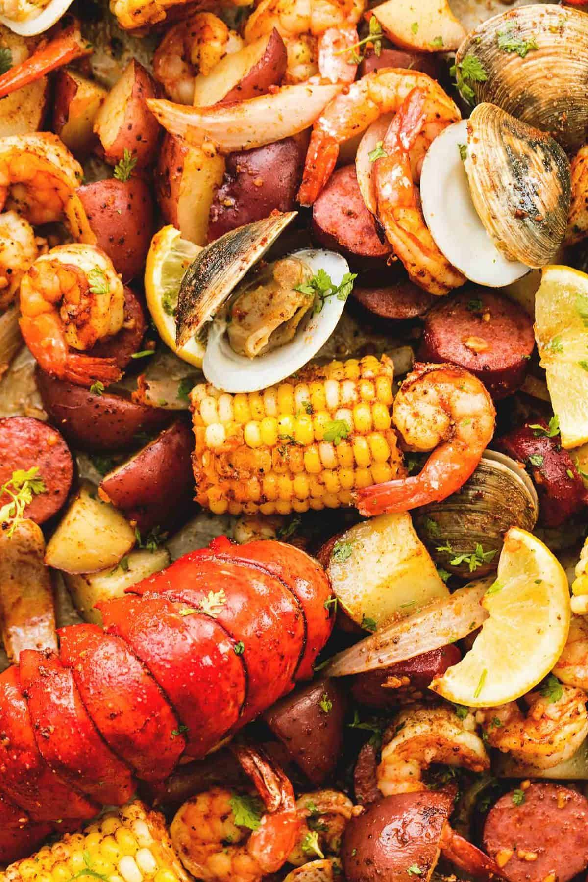 Sheet pan clambake with flavorful shrimp, sausage, lobster tails, clams, and veggies all made on one pan. The easiest, tastiest way to enjoy a clambake!