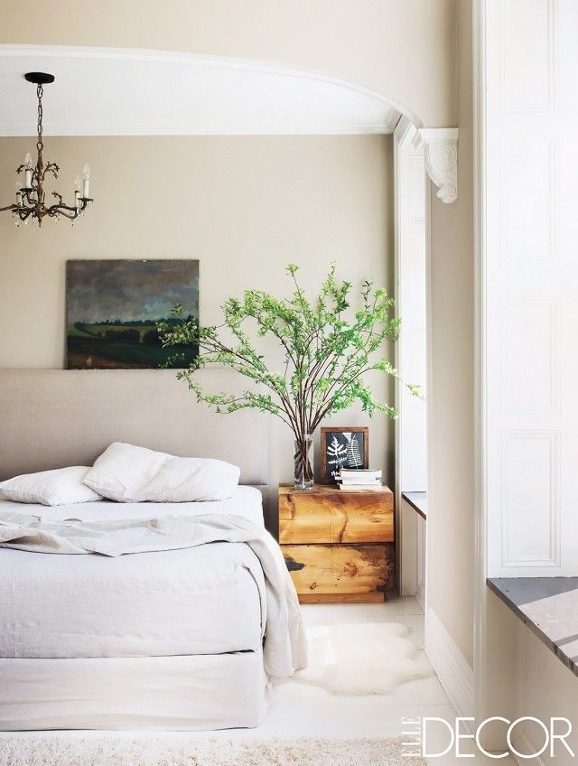 Neutral bedroom with a chandelier, art, and natural hues