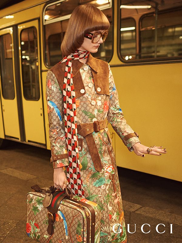 Model Peyton Knight wears the Gucci Tian trench coat with suede details, a print silk scarf, square eyeglass frames with crystal ornaments and Web temples, and a Gucci Tian suitcase.