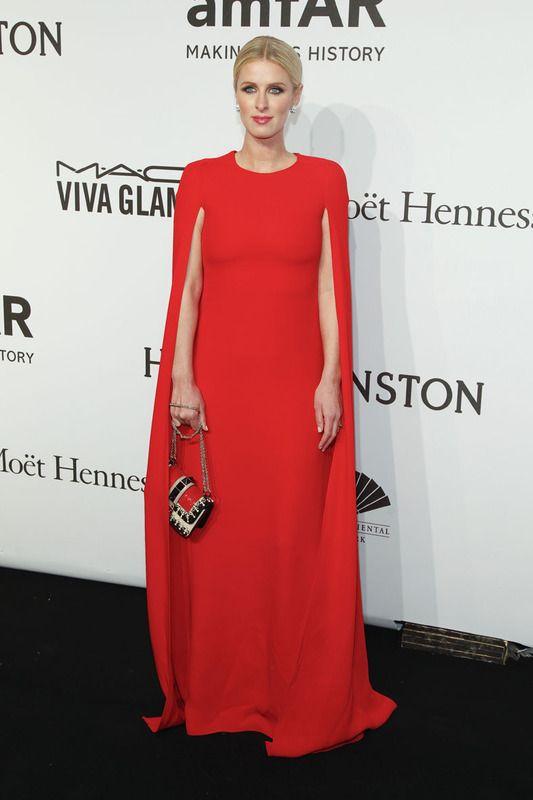 Nicky Hilton elegantísima con este espectacular vestido capa en rojo combinado con un bolso tricolor. Perfecta también su elección en cuanto a joyas, peinado y maquillaje.