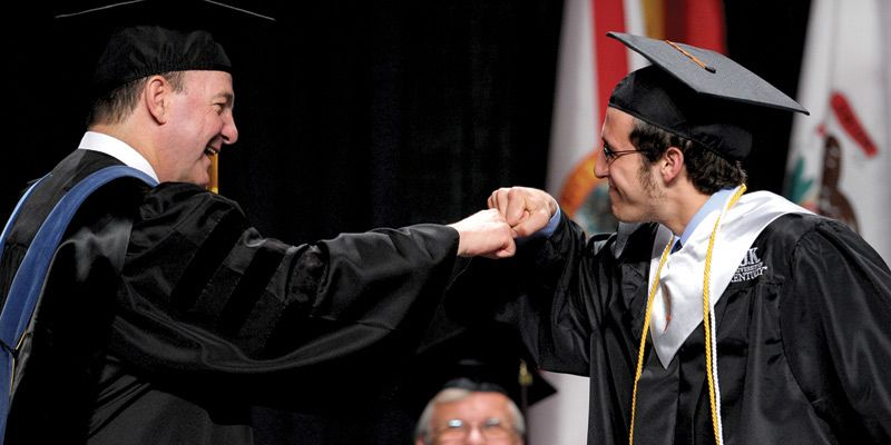 College of Engineering Dean Thomas Lester gives a congratulatory fist bump to Sam Nicaise at the 2010 Graduation ceremonies.