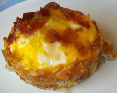 Press shredded hash browns into muffin tin; add shredded cheese & bake in oiled tin for 15 mins at 425. Reduce to 350 - add egg, bacon bits & top w/cheese.  Bake 15-18 addtl mins.