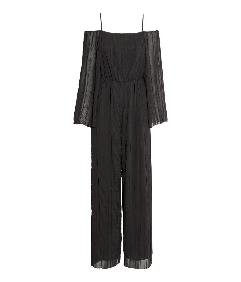 Sort. En plissért jumpsuit i chiffon med vide ermer og ben. Den har bare skuldre og smale skulderbånd. Dypt v-ringet rygg. Avskåret i midjen med elastikk. F