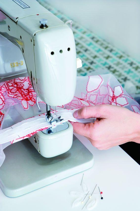 1. Buk stoffet foroven, og hæft gardinbåndet med nåle på bagsiden. Sy gardinbåndet fast i stoffet på symaskine. Båndet skal syes både foroven og forneden.