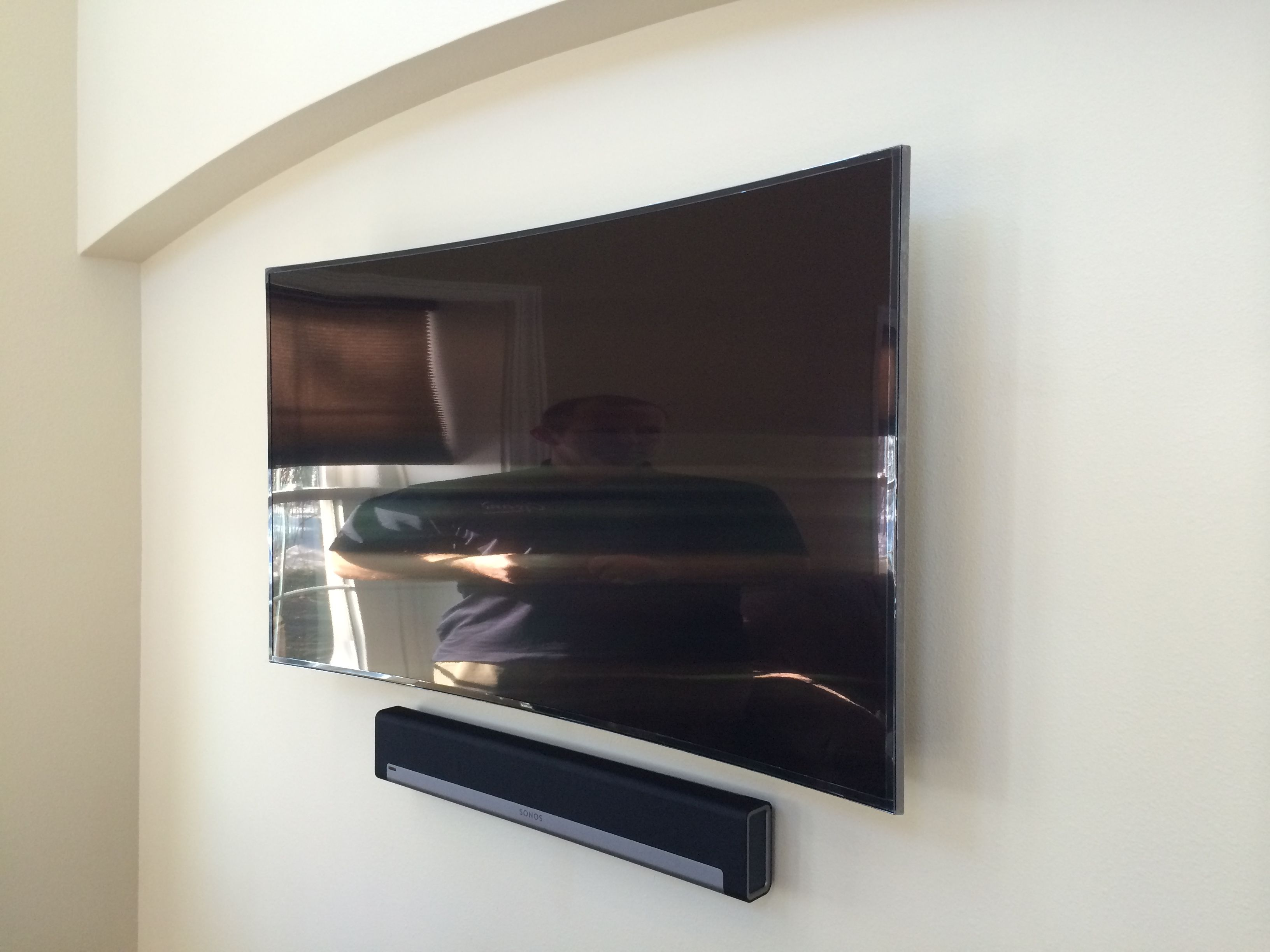 samsung curved tv in living room. curved flat panel tv mounted on a wall with sonos playbar home theater soundbar system samsung tv in living room c