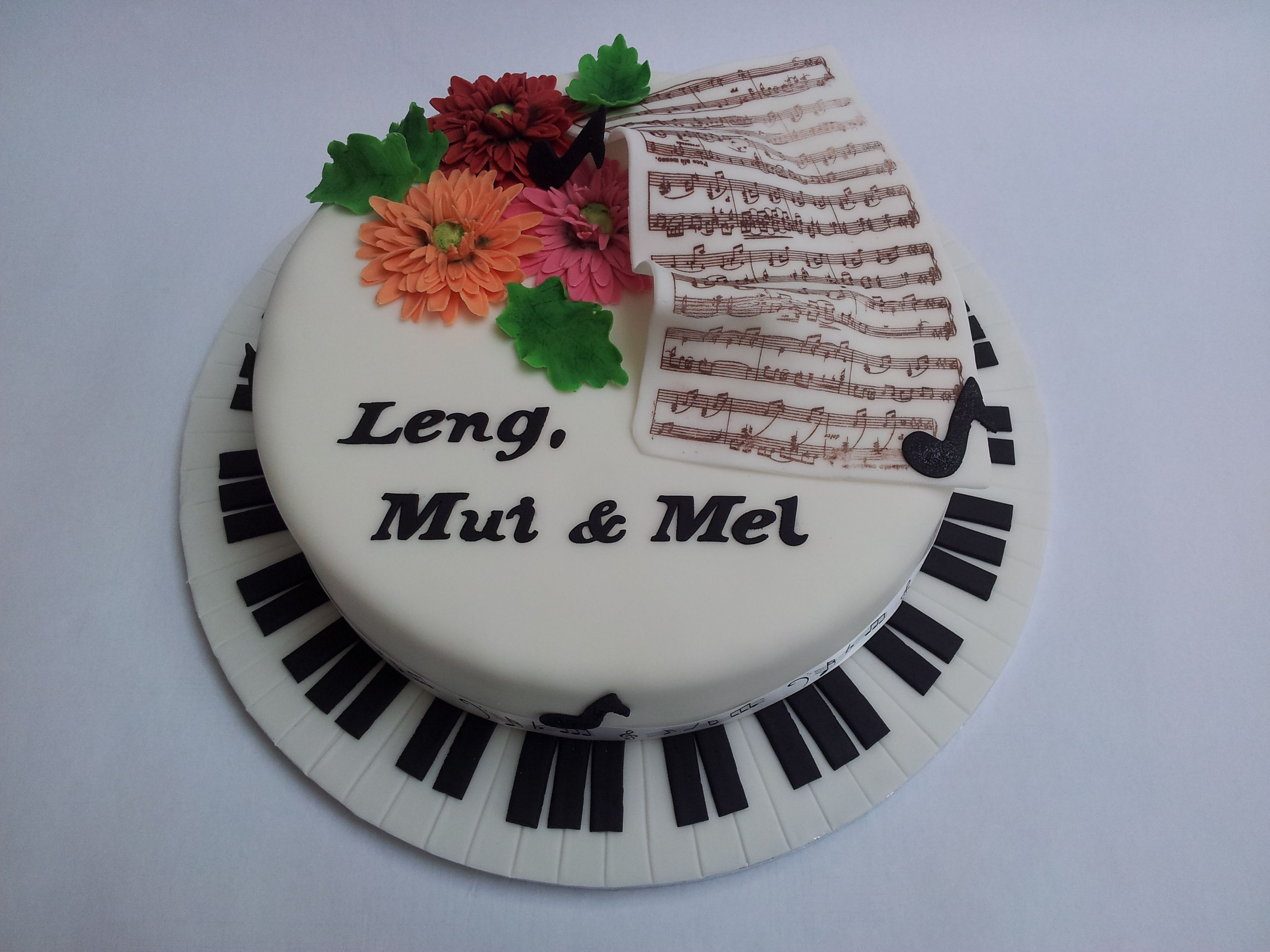 - Musical notes cake with gerbera daisies.  The sheet music was done using a transfer sheet.